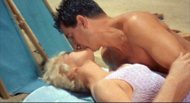 Doris Day and Rock Hudson kiss on the beach during a romantic moment in Lover Come Back.