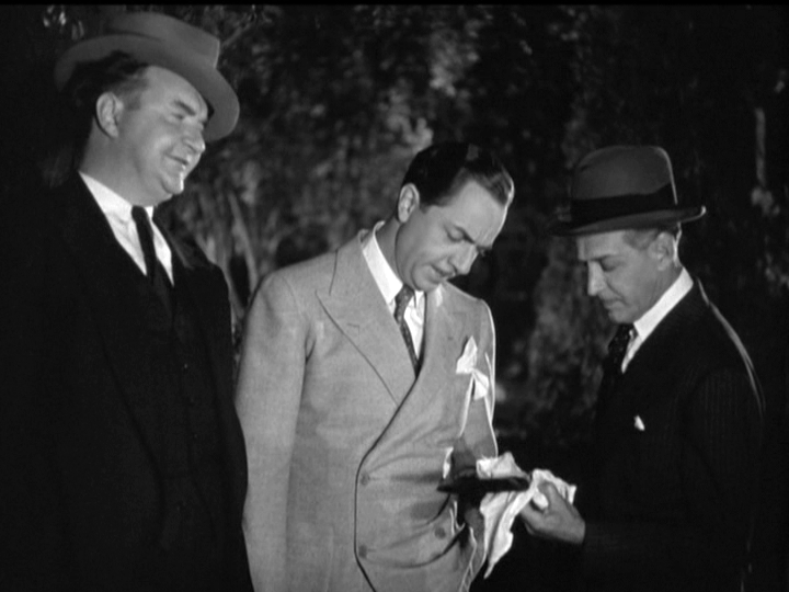 NIck Charles (William Powell) surveys the murder weapon with two detectives.