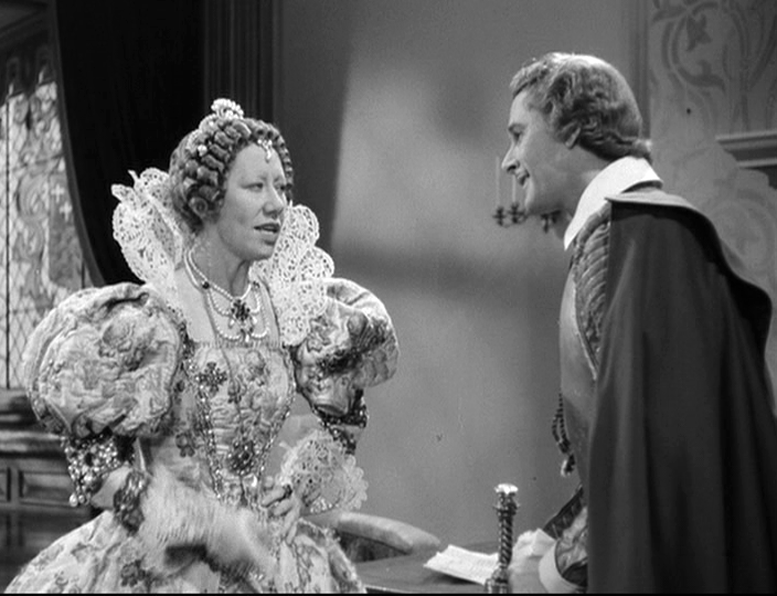Queen Elizabeth I (Flora Robson) and Captain Thorpe (Errol Flynn) debate his next steps.