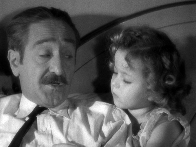Adolphe Menjou is becoming captivated by Little Miss Marker.