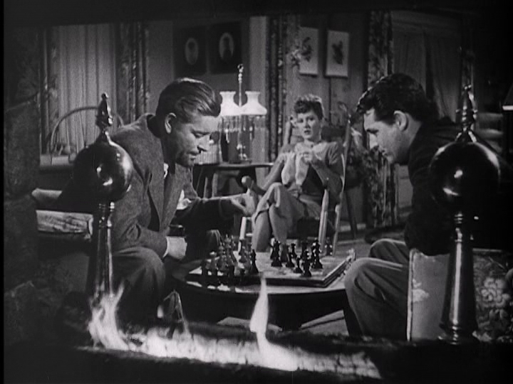 "Ronald Colman, Jean Arthur, and Cary Grant enjoy a quiet evening of chess and knitting in ""The Talk of the Town."""