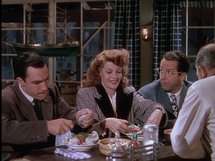 Gene Kelly, Rita Hayworth, and Phil Silvers search for pearls in their oysters.