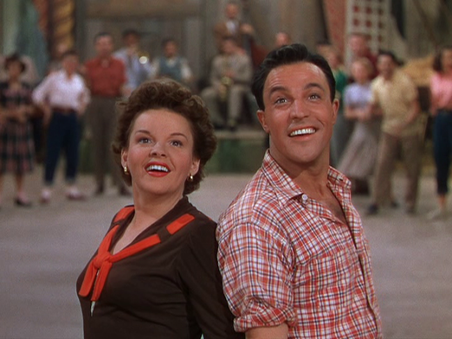 "Judy Garland and Gene Kelly smile at the finish of their performance in ""Summer Stock."""
